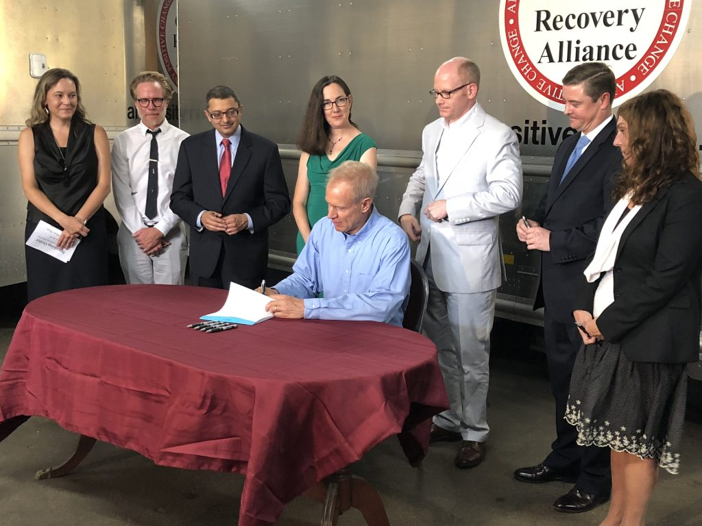 Gov. Bruce Rauner signs the Alternatives to Opioids Act Tuesday at the Chicago Recovery Alliance. | Lisa Mann for Sun-Times