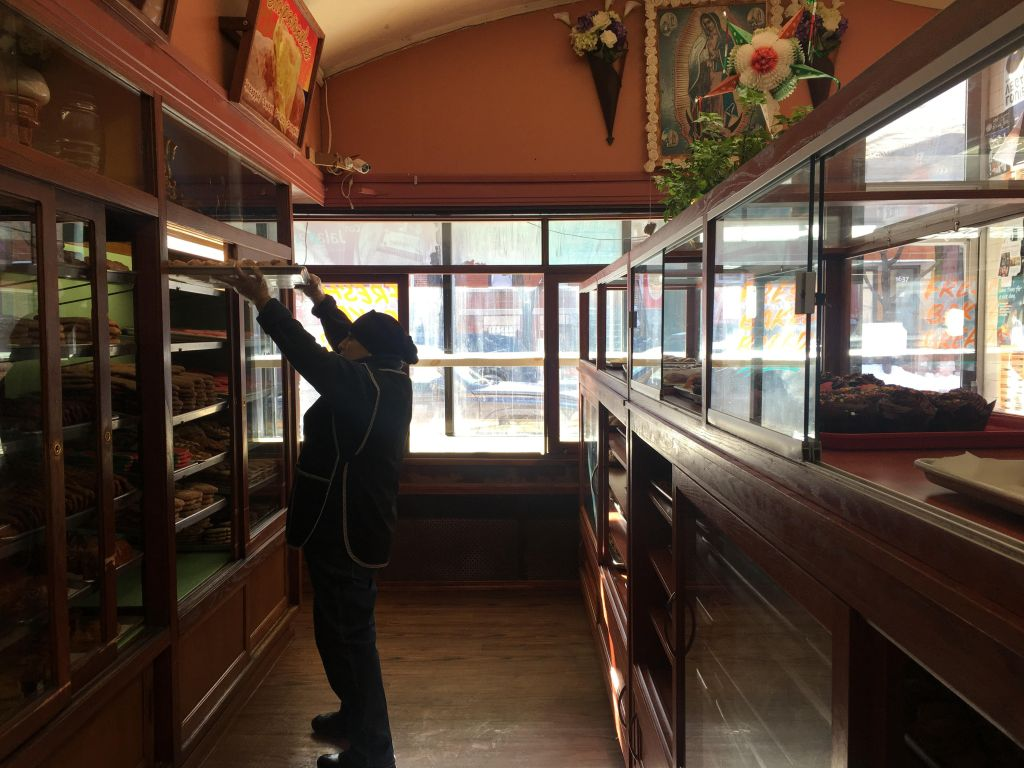 A worker at Panaderia Nuevo Leon moving a tray of sweet bread.
