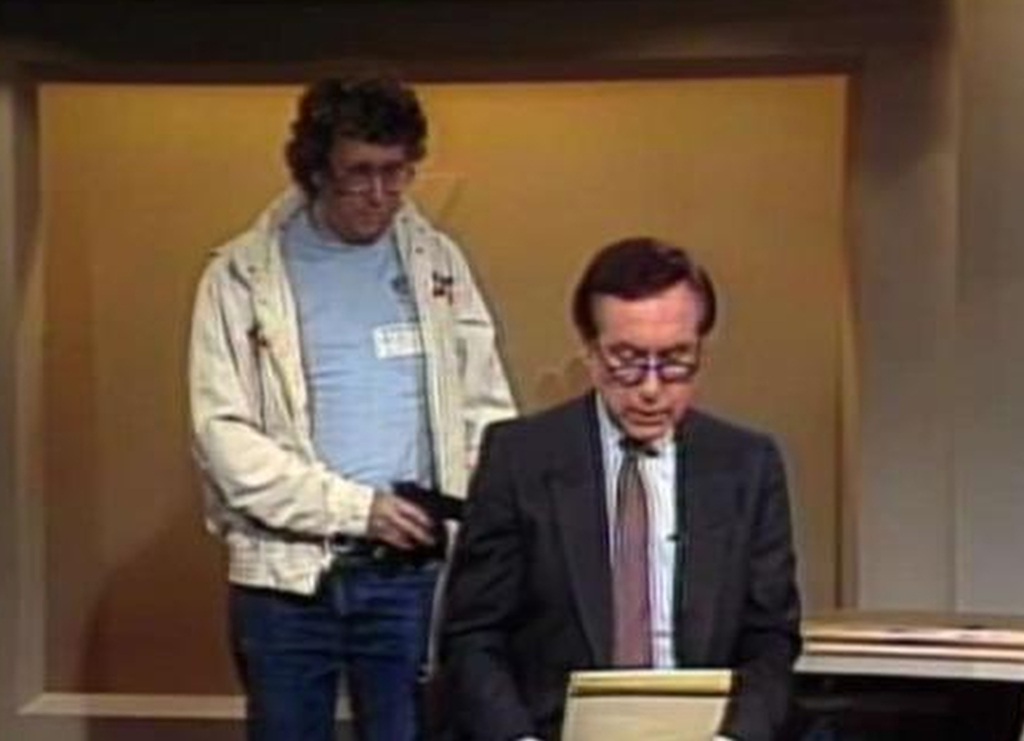 This Aug. 20, 1987, image made from video shows an intruder with a gun, as journalist David Horowitz is taken hostage during a live broadcast of Channel 4 Los Angeles. Horowitz remained calm and read the gunman's statements on camera. The gun turned out to be a toy BB gun, and Horowitz then took on the campaign to ban toy guns that look like real guns. | NBC-TV via AP