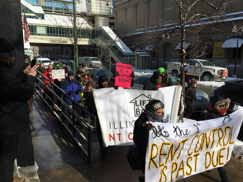Protesters march down North Clinton Avenue on Friday across from the corporate offices Pangea Properties, a real estate management company.