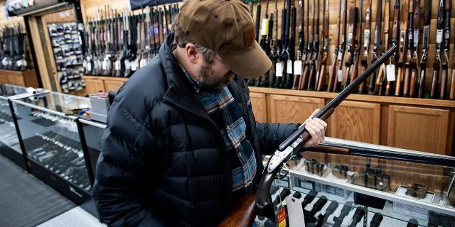 A customer looks at an antique shotgun at Cherry's Outdoor World in Ottawa, Ohio, Jan. 23, 2020. (Photo by BRENDAN SMIALOWSKI/AFP via Getty Images)
