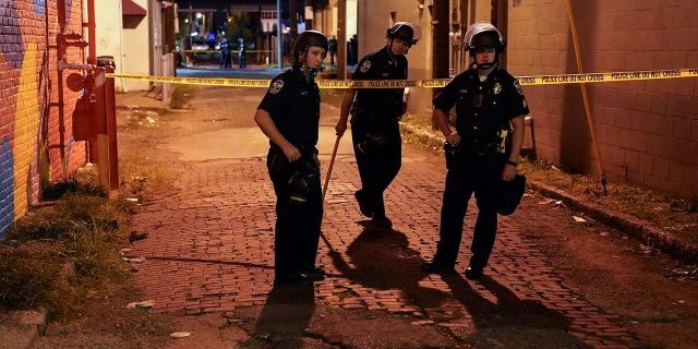 Police survey an area after a police officer was shot, Wednesday, Sept. 23, 2020, in Louisville, Ky. (AP Photo/John Minchillo)