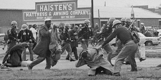 A state trooper swings a billy club at John Lewis, right foreground, chairman of the Student Nonviolent Coordinating Committee, to break up a civil rights voting march in Selma, Ala. (AP Photo/File)