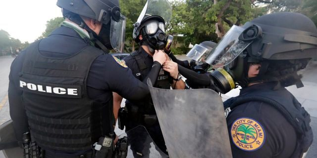 City of Miami police officers gear up as they prepare for any problems with protesters Sunday, May 31, 2020, in Miami. (AP Photo/Wilfredo Lee)
