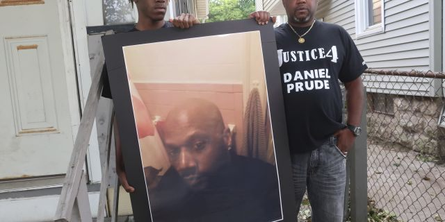 In this Sept. 3, 2020, file photo, Joe Prude, brother of Daniel Prude, right, and his son Armin, stand with a picture of Daniel Prude in Rochester, N.Y. (AP Photo/Ted Shaffre, File)