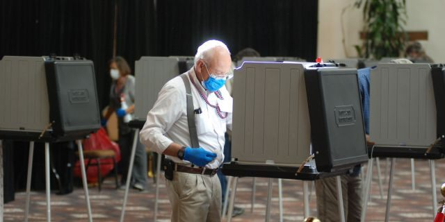 Temporary election worker Joseph Banar disinfects voting stations as a precaution against the coronavirus...on Tuesday, Oct. 6, 2020, in Santa Fe. (AP Photo/Morgan Lee)