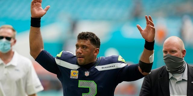 Seattle Seahawks quarterback Russell Wilson (3) raises his hands as fans cheer at the end of an NFL football game, Sunday, Oct. 4, 2020 in Miami Gardens, Fla. The Seahawks defeated the Dolphins 31-23.(AP Photo/Wilfredo Lee)