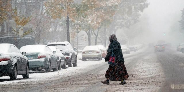 A pedestrian crosses a Minneapolis street as the first measurable snow of the season spread over much of Minnesota Tuesday, Oct. 20, 2020.
