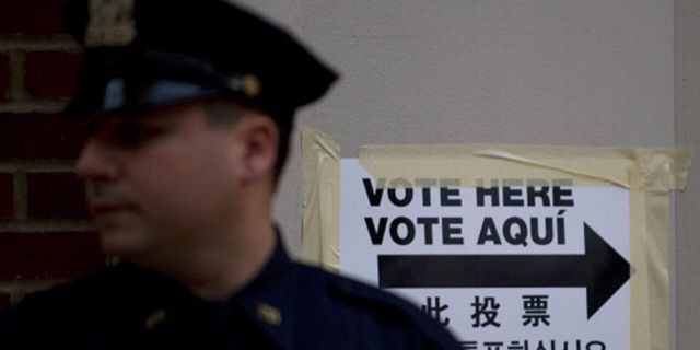 A New York City police officer stands guard outside a polling station in a public school Nov. 2, 2010 in New York. (DON EMMERT/AFP via Getty Images)