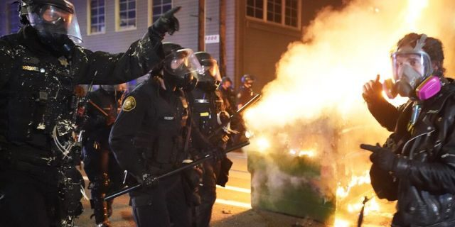 Portland police officers push protesters past a dumpster fire during a dispersal from in front of the Immigration and Customs Enforcement (ICE) detention facility in the early morning on August 21, 2020 in Portland, Ore. (Photo by Nathan Howard/Getty Images)