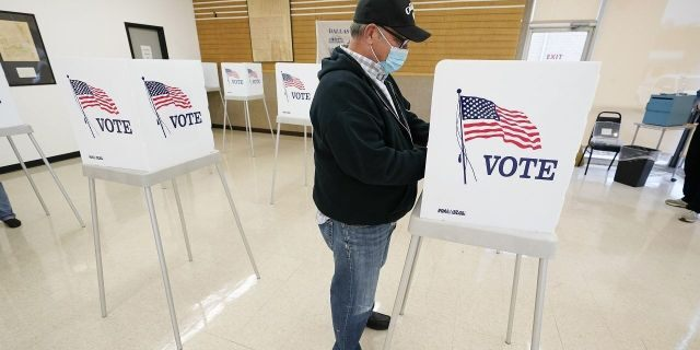 FILE - In this Oct. 20, 2020 file photo, Kelly Wingfield, of Urbandale, Iowa, fills out his ballot during early voting in the general election, in Adel, Iowa. (AP Photo/Charlie Neibergall, File)