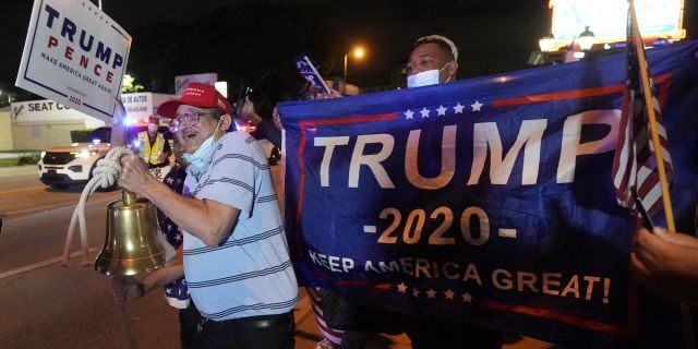 Rafael Fagundo rings a bell as he and other supporters of President Donald Trump chant and wave flags outside the Versailles Cuban restaurant during a celebration on election night, Tuesday, Nov. 3, 2020, in the Little Havana neighborhood of Miami. (AP Photo/Wilfredo Lee)