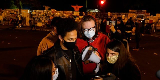 A reporter, right, shows a video feed of President Donald Trump to people at Black Lives Matter Plaza, Wednesday, Nov. 4, 2020, in Washington. (AP Photo/Jacquelyn Martin)