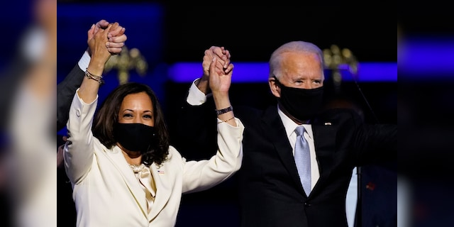 Vice President-elect Kamala Harris holds hands with President-elect Joe Biden and her husband, Doug Emhoff, as they celebrate Saturday, Nov. 7, 2020, in Wilmington, Del. (AP Photo/Andrew Harnik)