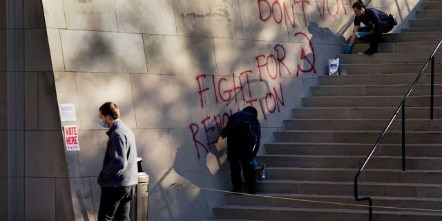 A man walks past police collecting evidence after graffiti was found outside a polling place at the National World War I museum Tuesday, Nov. 3, 2020, in Kansas City, Mo.