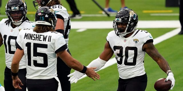 Jacksonville Jaguars running back James Robinson, right, celebrates his rushing touchdown with Gardner Minshew (15) during the first half of an NFL football game against the Los Angeles Chargers Sunday, Oct. 25, 2020, in Inglewood, Calif. (AP Photo/Alex Gallardo )