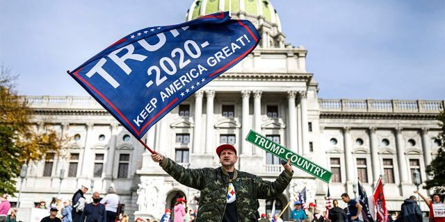 A man waves a flag at a pro-Trump rally at the Pennsylvania state Capitol in Harrisburg, Pa., Friday, Nov. 5, 2020. (Associated Press)