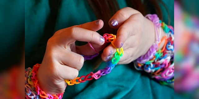 Hayley Orlinsky examines a bracelet she made from colorful rubber bands Wednesday, Dec. 2, 2020, in the bedroom of her Chicago home. The 7-year-old has spent most of the coronavirus pandemic crafting the bracelets as a fundraiser, earning nearly $20,000, to buy personal protective equipment for the Ann and Robert H. Lurie Children's Hospital. (AP Photo/Charles Rex Arbogast)