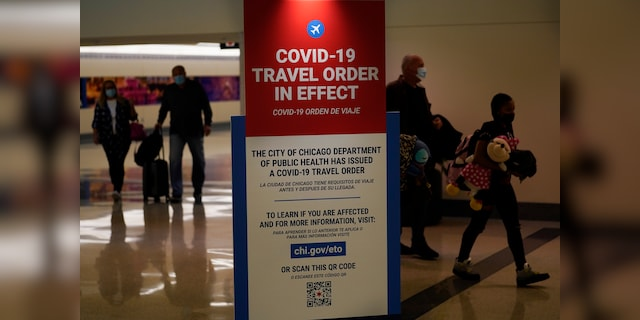 Travelers arriving at Midway Airport in Chicago are reminded of the city's COVID-19 travel orders in this Nov. 24 photo. (AP Photo/Charles Rex Arbogast, File)
