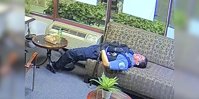 In this file still image taken from security video released by the Congressman Bobby Rush's Campaign Office, a Chicago police officer lies on a couch inside Rush's burglarized congressional campaign office in Chicago on Sunday, May 31, 2020. Chicago Police suspended several officers captured on video during 2020's widespread unrest who were lounging, and apparently even sleeping, inside a burglarized congressional campaign office as people citywide vandalized and stole from businesses, a police union official said, Thursday, Jan. 14, 2021