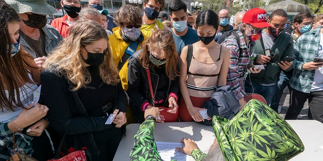 """A man wearing a cannabis costume hands out marijuana cigarettes in New York during a """"Joints for Jabs"""" event, where adults who showed their COVID-19 vaccination cards received a free joint. (AP Photo/Mark Lennihan, File)"""