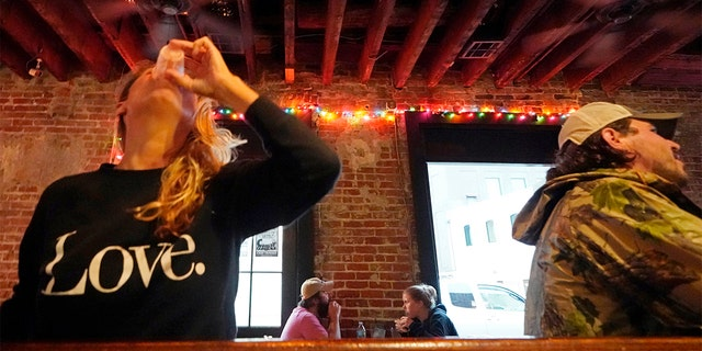 In this Tuesday, April 13, 2021 file photo, Allison Richter drinks her free shot at the bar, after receiving the Moderna COVID-19 vaccine, during a vaccine event. (AP Photo/Gerald Herbert)