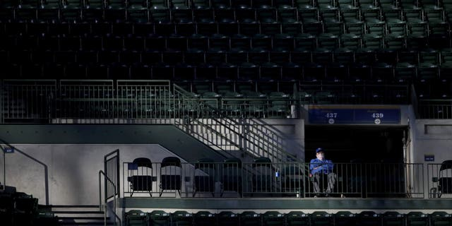 A fan watches from the stands during the second inning of a baseball game between the Milwaukee Brewers and the St. Louis Cardinals on Tuesday, May 11, 2021, in Milwaukee. (AP Photo/Aaron Gash)