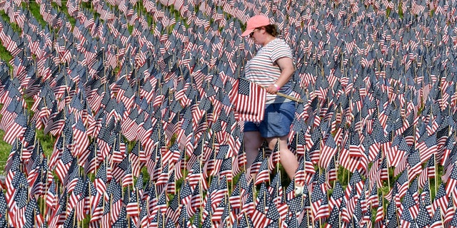 A volunteer walks through a field of American flags planted on Boston Common Wednesday, May 26, 2021, in Boston. (AP Photo/Josh Reynolds)