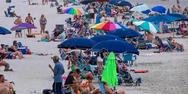 Beachgoers gather in the Cherry Grove section of North Myrtle Beach, S.C., Saturday, May 29, 2021. (Jason Lee/The Sun News via AP)