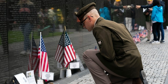 Army Spc. Joseph Wolfe reads the names of the fallen soldiers at Vietnam Veterans Memorial at the National Mall ahead of Memorial Day, in Washington, Sunday, May 30, 2021. (AP Photo/Jose Luis Magana)