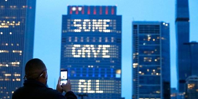 """A person takes a photo, Sunday, May 30, 2021, of an illuminated sign on Chicago's Blue Cross Blue Shield Tower displaying """"Some Gave All"""" in honor of Memorial Day. (AP Photo/Shafkat Anowar)"""