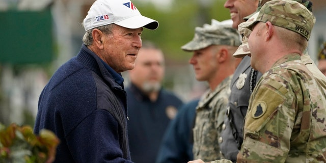 Former President George W. Bush thanks members of the American Legion Post 159 firing squad after a Memorial Day service in Kennebunkport, Maine, Monday, May 31, 2021. (AP Photo/Robert F. Bukaty)