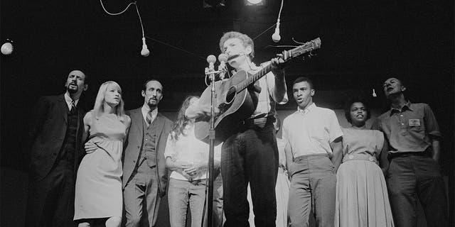 American musician Bob Dylan plays acoustic guitar and harmonica during a performance at the Newport Folk Festival, Newport, Rhode Island, July 1963. Among those behind him are, from left, Peter Yarrow, Mary Travers (1936 - 2009, Paul Stookey, Joan Baez (partially obscured), two unidentified people, Charles Neblett, Rutha Harris, and Pete Seeger (1919 - 2014).