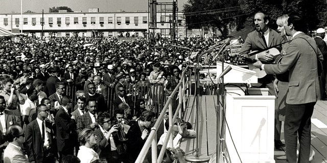American folk and pop group Peter, Paul and Mary perform during the March on Washington for Jobs and Freedom, Washington DC, August 28, 1963. The trio behind the microphone features, from left, Paul Stookey, Mary Travers (1936 - 2009), and Peter Yarrow. The march and rally provided the setting for the Reverend Martin Luther King Jr's iconic 'I Have a Dream' speech.
