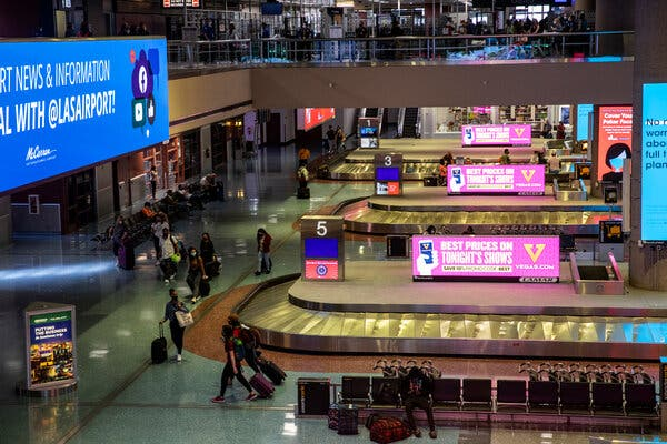 Americans whose passports expired overseas during the pandemic can use them to get home, the State Department said. Passengers walked through the baggage claim area at the Las Vegas airport.