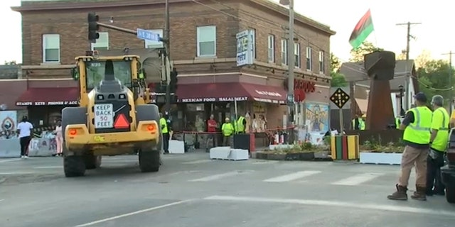Minneapolis city workers seen in George Floyd Square early Thursday.
