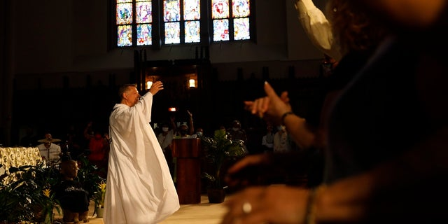 Parishioners raise their hands as Rev. Michael Pfleger conducts his first Sunday church service as a senior pastor at St. Sabina Catholic Church following his reinstatement by Archdiocese of Chicago after decades-old sexual abuse allegations against minors, Sunday, June 6, 2021, in the Auburn Gresham neighborhood in Chicago. (AP Photo/Shafkat Anowar)