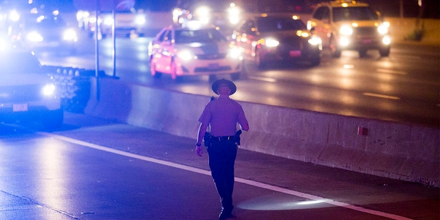 A member of the Illinois State Police looks for evidence on the Eisenhower Expressway where two people were wounded in a shooting Saturday, Aug. 13, 2016, in Chicago. (Armando L. Sanchez/Chicago Tribune/Tribune News Service via Getty Images)