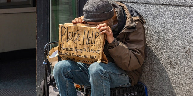 Homeless man holding a cardboard sign, asking for help in downtown, Manhattan, New York City, on May 2, 2019.