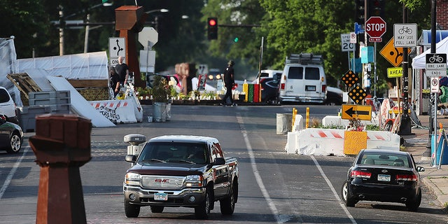 A vehicle travels along Chicago Ave. S. near East 38th Street at George Floyd Square, Tuesday, June 8, 2021, in Minneapolis, after city crews returned to remove debris and barriers for the second time in an attempt to open the intersection to traffic. (David Joles/Star Tribune via AP)