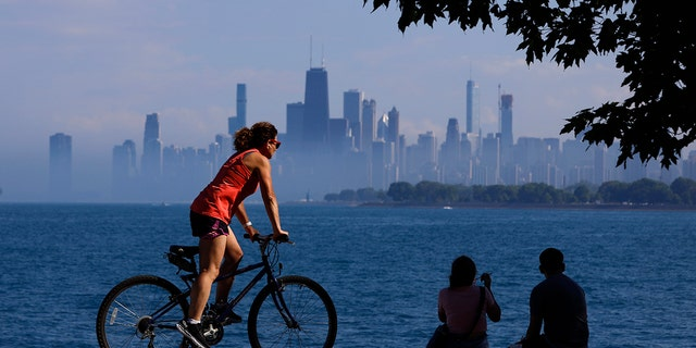 People spend time as they take advantage of warm summer weather along Lake Michigan, Wednesday, June 9, 2021 in Montrose Beach in Chicago. The beaches in Chicago have reopened since closing over a year ago because of the coronavirus pandemic. (AP Photo/Shafkat Anowar)