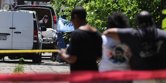 People watch as the body of a shooting victim is loaded into a van on June 15, 2021, in the Englewood neighborhood of Chicago. (Photo by Scott Olson/Getty Images)