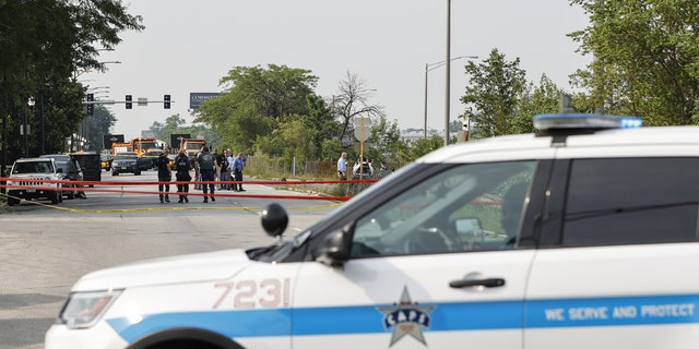 Law enforcement officers investigate a crime scene near the border between the Morgan Park and West Pullman neighborhoods on July 7, 2021 in Chicago, Illinois. (Photo by Kamil Krzaczynski/Getty Images)