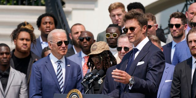 President Joe Biden, surrounded by members of the Tampa Bay Buccaneers, listens as Tampa Bay Buccaneers quarterback Tom Brady speaks during a ceremony on the South Lawn of the White House, in Washington, Tuesday, July 20, 2021. (AP Photo/Manuel Balce Ceneta)