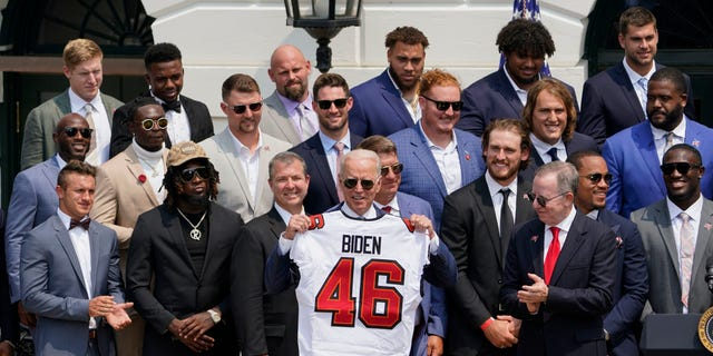 President Joe Biden, surrounded by members of the Tampa Bay Buccaneers, poses for a photo holding a jersey during a ceremony on the South Lawn of the White House, in Washington, Tuesday, July 20, 2021(AP Photo/Andrew Harnik)