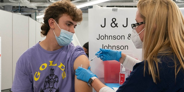 In this July 30, 2021, file photo, Bradley Sharp, of Saratoga, N.Y., gets the Johnson & Johnson vaccine from registered nurse Stephanie Wagner in New York. Sharp needs the vaccination because it is required by his college. Hundreds of college campuses across the country have told students that they must be fully vaccinated against COVID-19 before classes begin in a matter of weeks. (AP Photo/Mark Lennihan, File)