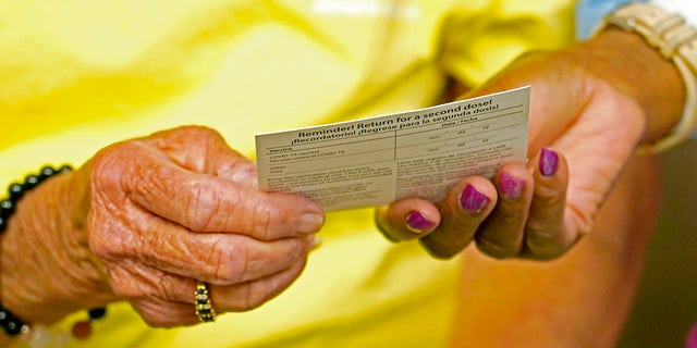A woman receives a vaccination card after receiving a shot of the Johnson & Johnson COVID-19 vaccine. (AP Photo/Rogelio V. Solis)