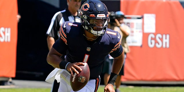Chicago Bears quarterback Justin Fields runs with the ball during the first half of an NFL preseason football game against the Miami Dolphins in Chicago, Saturday, Aug. 14, 2021.