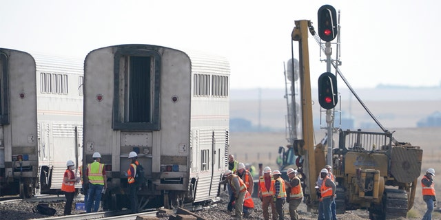 Workers examine a train car, Monday, Sept. 27, 2021, from an Amtrak train that derailed Saturday, near Joplin, Mont.