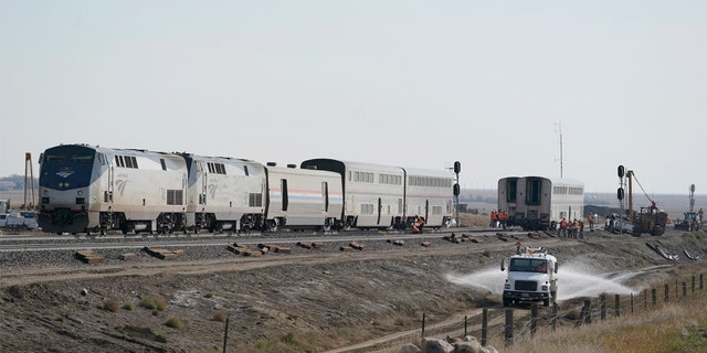 A water truck drives on a road, Monday, Sept. 27, 2021, next to an Amtrak train that derailed Saturday, near Joplin, Mont., killing three people and injuring others.